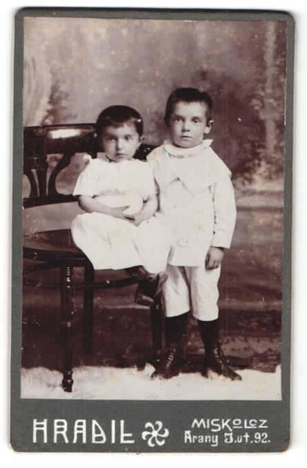 Fotografie Hradil, Miskolcz, kleines niedliches Mädchen im weissen Kleid & frecher Knabe im weissen Anzug