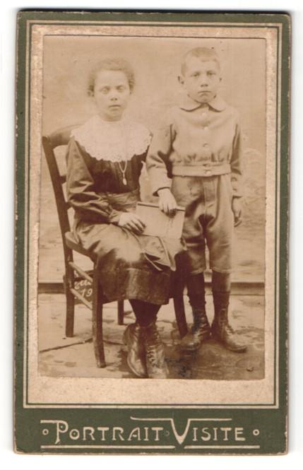 Fotografie Portrait Visite, Ort unbekannt, hübsches Mädchen im Kleid & frecher Bube im Anzug mit Buch