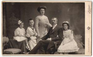Fotografie Pietzner, Wien, Familie elegant gekleidet im Foto-Atelier, Knabe in Marineuniform