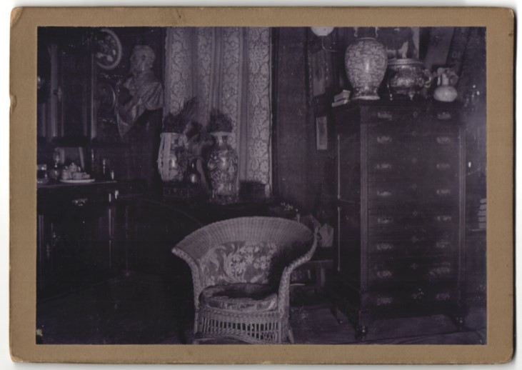 Fotografie Wohnzimmer-Einrichtung, Korbsessel, Anrichte mit antiken Vasen, Büste