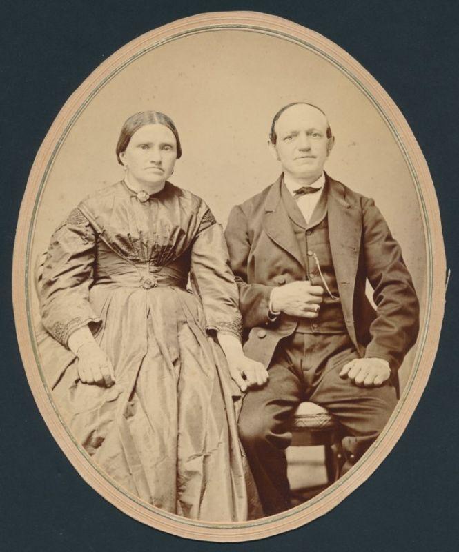 Fotografie Paar im feinen Zwirn posiert sitzend im Foto-Atelier