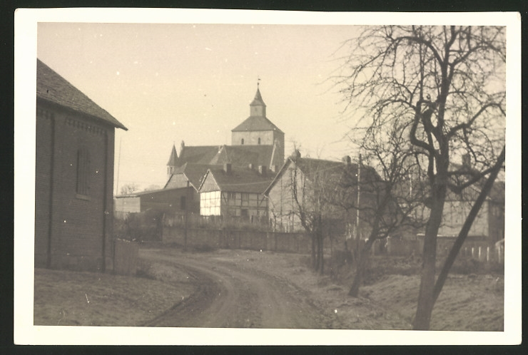 Fotografie Fotograf unbekannt, Ansicht Fachwerkhaus und Kirche in einem Ort