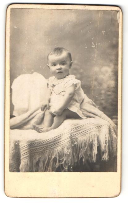 Fotografie Fotograf & Ort unbekannt, niedliches Baby im weissen Kleid auf Decke sitzend