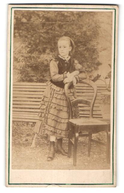 Fotografie Fotograf & Ort unbekannt, junges Mädchen im hübschen Rüschenkleid am Stuhl stehend