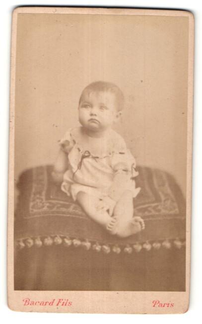 Fotografie Bacard Fils, Paris, niedliches Baby im weissen Kleid auf Kissen sitzend
