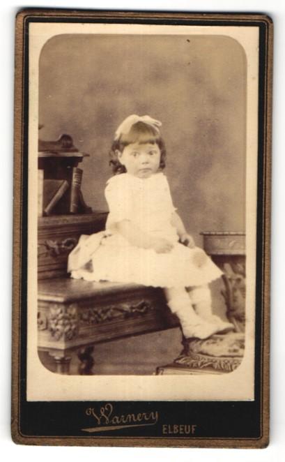 Fotografie Warnery, Elbeuf, niedliches kleines Mädchen mit Haarschleife im weissen Kleid