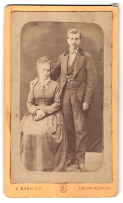 Fotografie E. Bernier, Paris, junge hübsche Frau im edlen Kleid & Mann im edlen Anzug mit Schleife