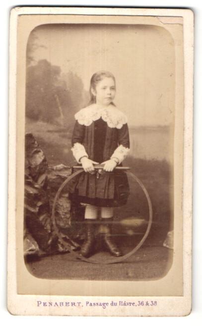 Fotografie Penabert, Paris, niedliches Mädchen im hübschen Kleid mit Reifen