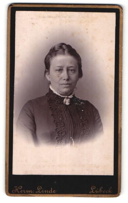 Fotografie Herm. Linde, Lübeck, Portrait edle Dame mit Flechtfrisur und Brosche am Kragen