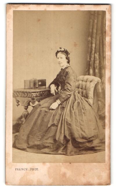 Fotografie Franck, Paris, hübsche Dame im prachtvollen Kleid am Tisch sitzend
