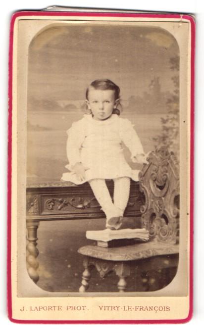 Fotografie J. Laporte, Vitry-le-Francois, Portrait kleines Mädchen auf Tisch sitzend