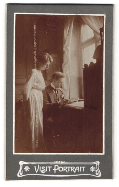 Fotografie junges Paar lesend am Fenster