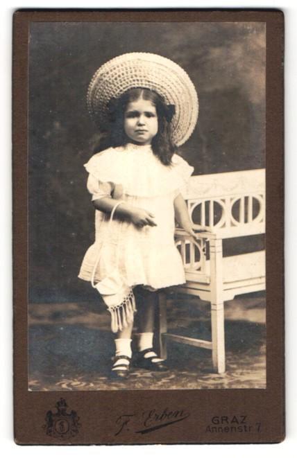 Fotografie F. Erben, Graz, kleines dunkelhaariges Mädchen mit grossem Hut und Tasche