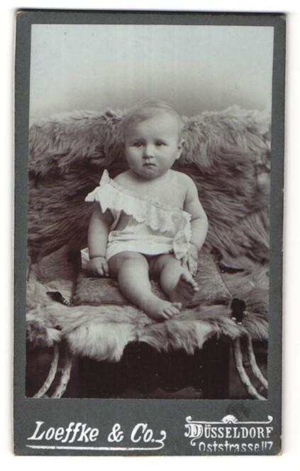 Fotografie Loeffke & Co., Düsseldorf, niedliches Baby auf Felldecke sitzend