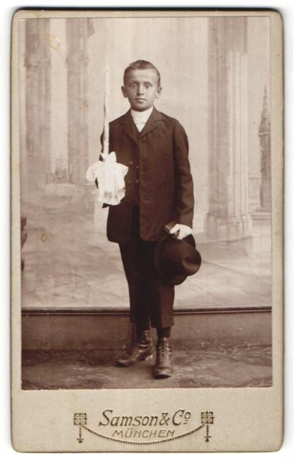 Fotografie Samson & Co, München, Portrait Knabe in feierlicher Kleidung mit Kerze und weit aufgerissenen Augen