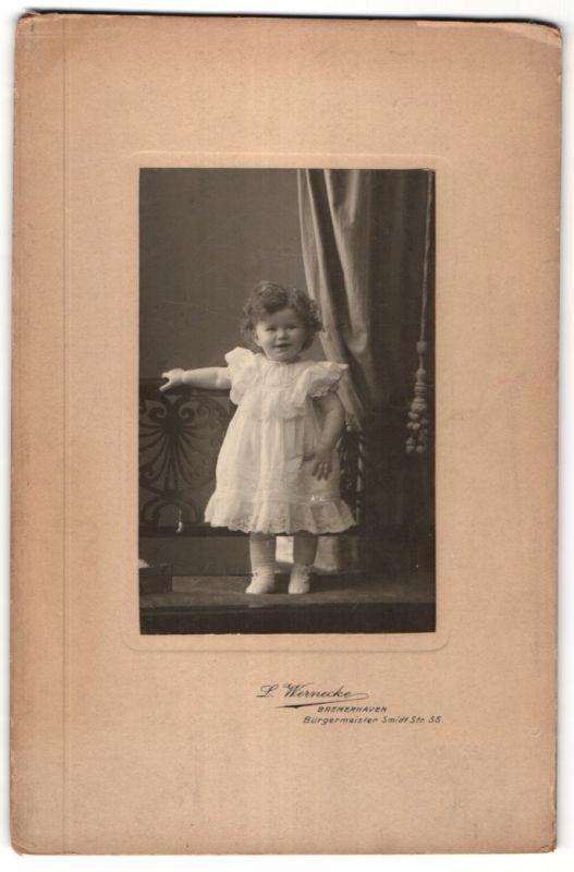 Fotografie L. Wernecke, Bremerhaven, Portrait lachendes Kleinkind in Kleidchen