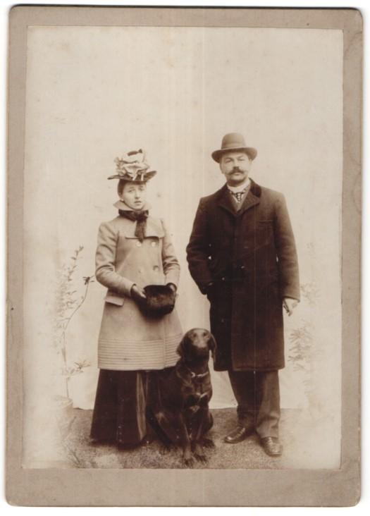 Fotografie Paar im feinen Zwirn mit Hund, Dame trägt Muff & Hut