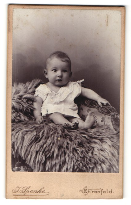 Fotografie J. Spenke, Ehrenfeld, Portrait Säugling mit nackigen Füssen