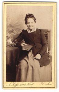 Fotografie A. Hoffmann, Dresden, ältere Dame mit Rüschenhaube und Buch am Tisch sitzend