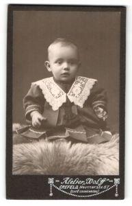 Fotografie Atelier Wolff, Crefeld, niedliches Baby auf Felldecke sitzend