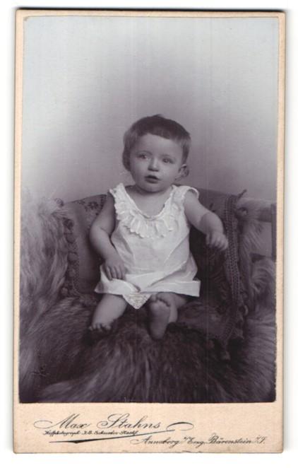 Fotografie Max Stahns, Annaberg / Erzgeb., niedliches kleines Mädchen auf Felldecke sitzend