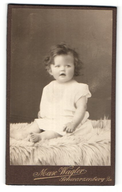 Fotografie Max Wagler, Schwarzenberg i. Sa., niedliches dunkelhaariges Mädchen auf Felldecke sitzend