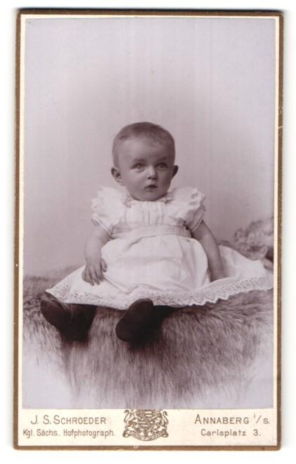 Fotografie J. S. Schroeder, Annaberg i. S., niedliches Baby auf Felldecke sitzend