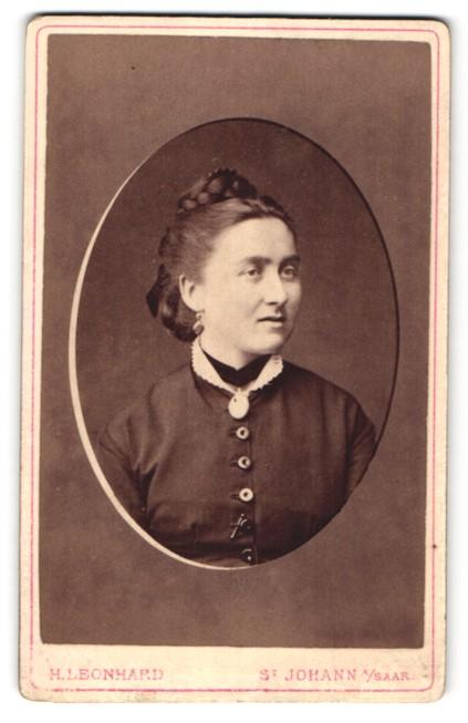 Fotografie H. Leonhard, St. Johann / Saar, Portrait hübsche Dame mit Flechtfrisur und Brosche