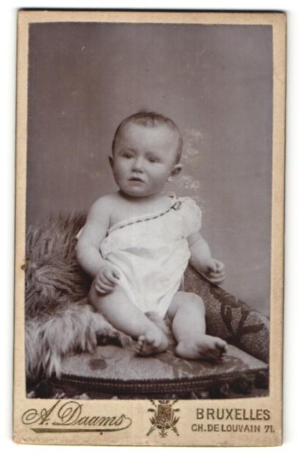 Fotografie A. Daams, Bruxelles, niedliches Baby auf Felldecke sitzend