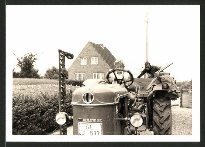 Fotografie Traktor Deutz, Knabe steuert Schlepper mit Mähwerk