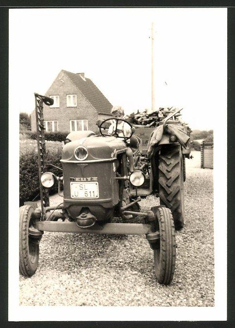 Fotografie Traktor Deutz, Knabe steuert Schlepper mit Mähwerk und Anhänger