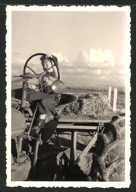 Fotografie Traktor, Knabe am Lenkrad eines Schlepper's