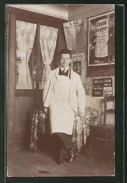 Foto-AK Friseur in Geschäft mit französ. Zeitungsseiten und Plaketen an der Wand