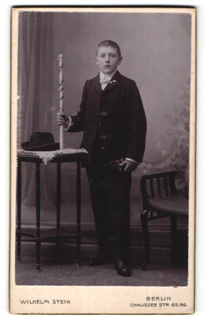 Fotografie Wilhelm Stein, Berlin, Portrait Knabe in festlicher Kleidung mit Kerze