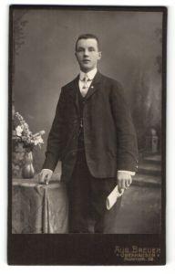 Fotografie Aug. Breuer, Oberhausen, junger Mann am Tisch mit Blumenvase stehend