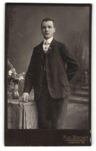 Fotografie Aug. Breuer, Oberhausen, junger Mann im edlen Anzug am Tisch stehend