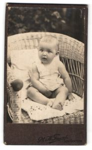 Fotografie Ph. & W. Freund, Schlüchtern, niedliches Baby im Korbsessel sitzend
