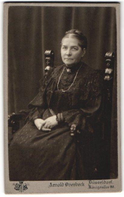Fotografie Arnold Overbeck, Düsseldorf, ältere hübsche Dame im prachtvollen Kleid mit Halskette