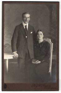 Fotografie Ph. & W. Freund, Schlüchtern, junges hübsches Paar mit Buch auf Stuhl sitzend
