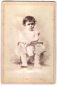 Fotografie unbekannter Fotograf und Ort, Portrait Kleinkind mit Holzspielzeug