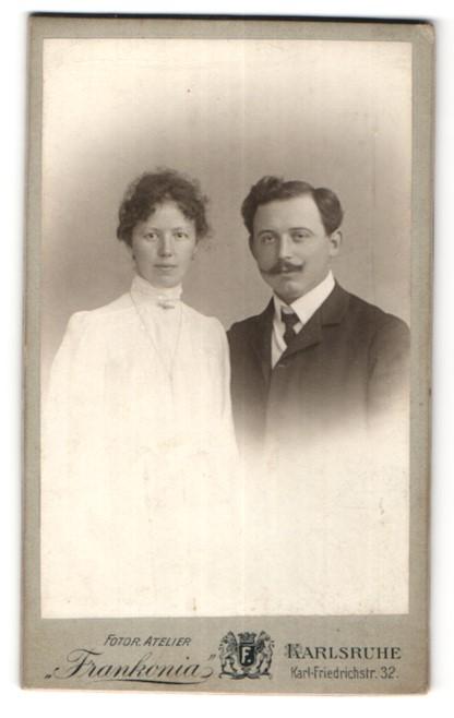 Fotografie Atelier Frankonia, Karlsruhe, Portrait hübsche Dame mit lockigem Haar & junger Mann mit Schnurrbart