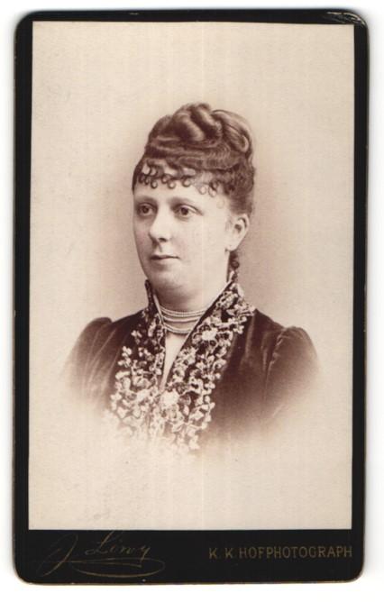 Fotografie J. Löwy, Wien, Portrait hübsche Dame mit Hochsteckfrisur, Perlenhalskette und Bluse mit Stickerei
