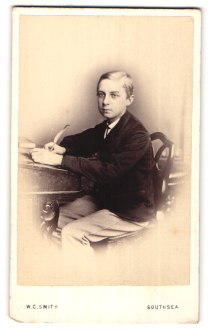 Fotografie W. C. Smith, Southsea, Portrait Knabe mit Schreibfeder am Tisch sitzend