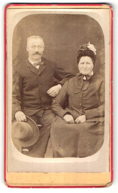 Fotografie Auguste Breuls, unbekannter Ort, Portrait betagtes Paar in zeitgenöss. Kleidung