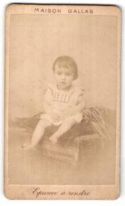Fotografie Maison Gallas, Ort unbekannt, niedliches kleines Mädchen mit brünetten Haaren auf Kissen sitzend