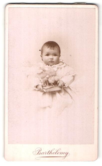 Fotografie Barthelemy, Nancy, niedliches dunkelhaariges Mädchen mit Spielzeug