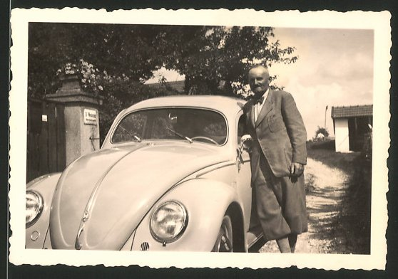 Fotografie Auto VW Käfer, stolzer Fahrer lehnt am Volkswagen PKW