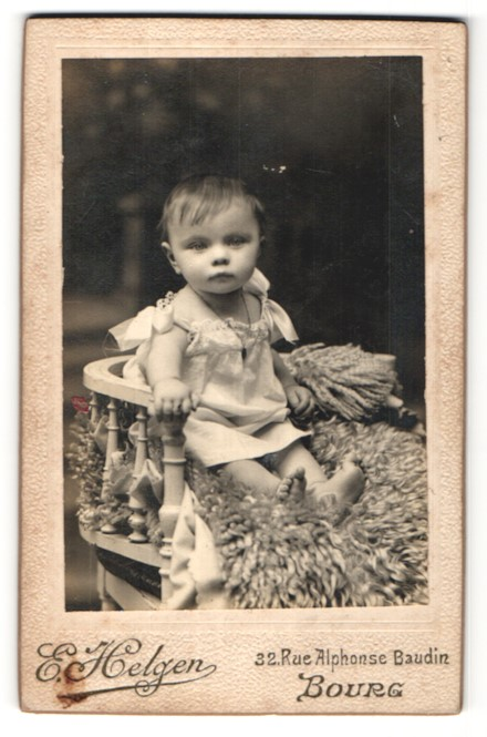 Fotografie E. Helgen, Bourg, freundliches kleines Mädchen mit Halskette auf Felldecke sitzend