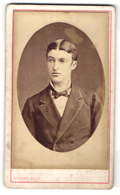 Fotografie Durand, Paris, Portrait junger dunkelhaariger Mann mit Mittelscheitel und Schleife im Anzug