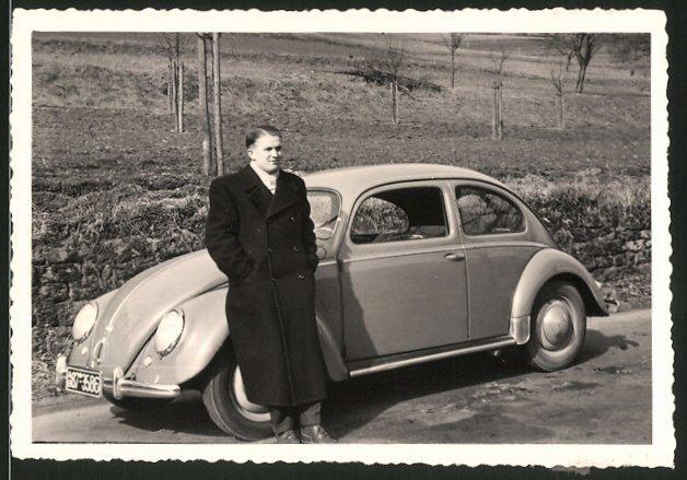 Fotografie Auto VW Käfer Brezel, Fahrer lehnt am Volkswagen PKW
